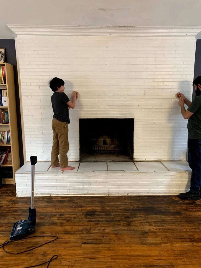 young boy standing on top a white fireplace