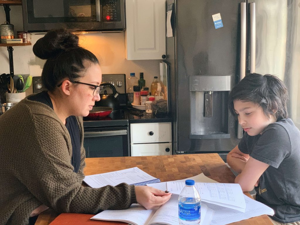 mother doing homeschool with son in kitchen
