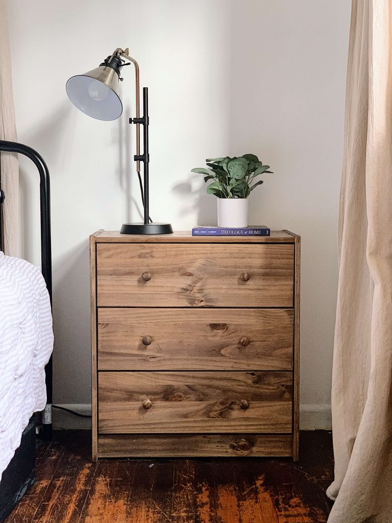 stained three drawer nightstand with lamp and plant
