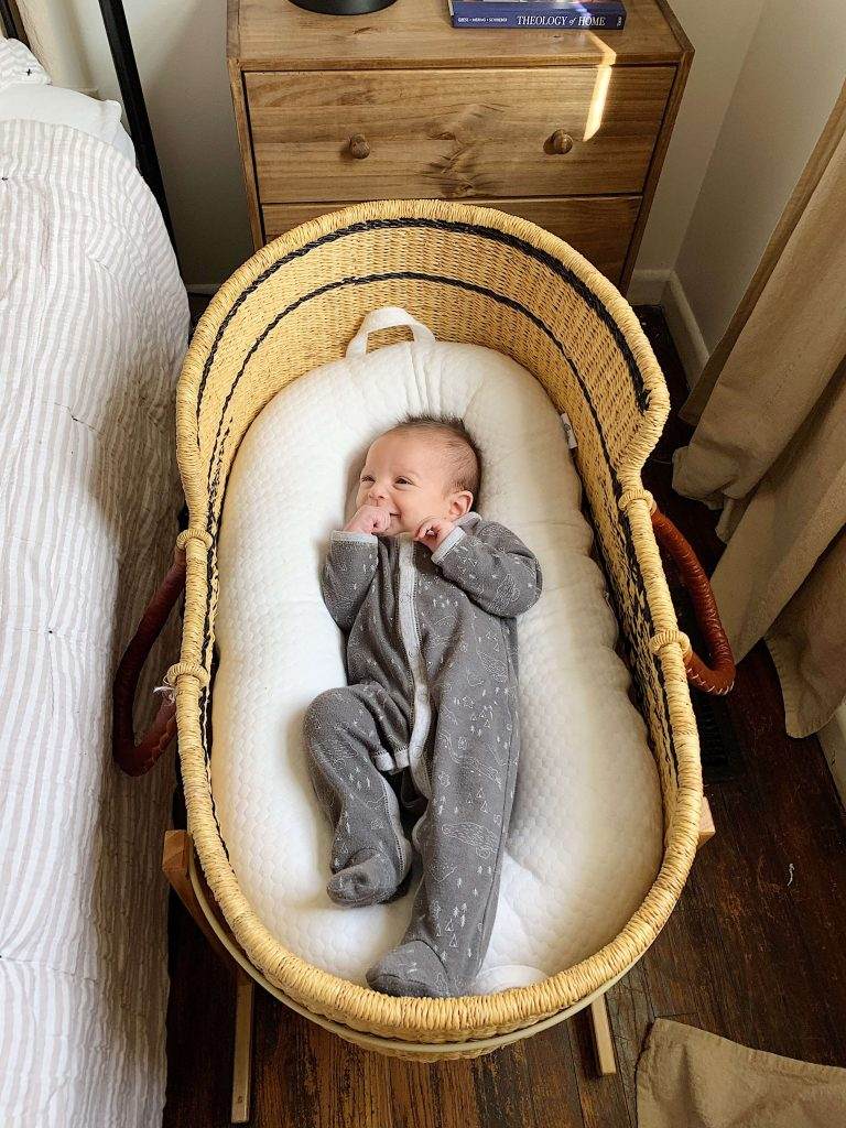 baby in gray sleeper laying in bassinet
