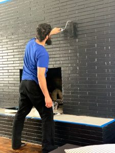 bearded man in blue shirt painting a fireplace black