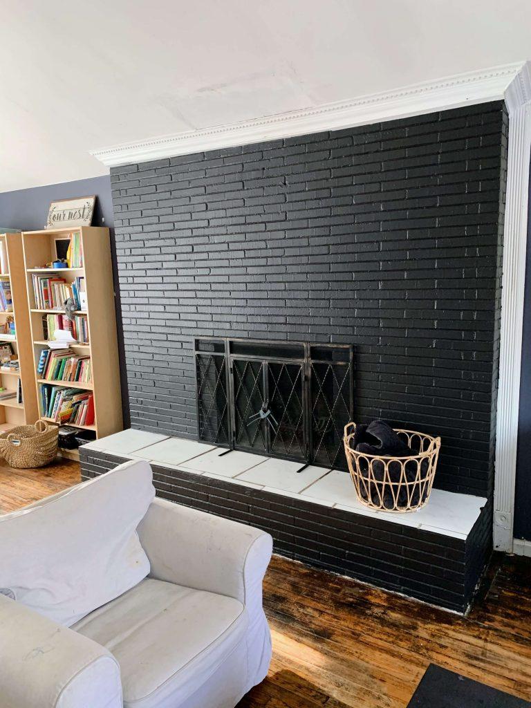 Wide brick fireplace painted matte black