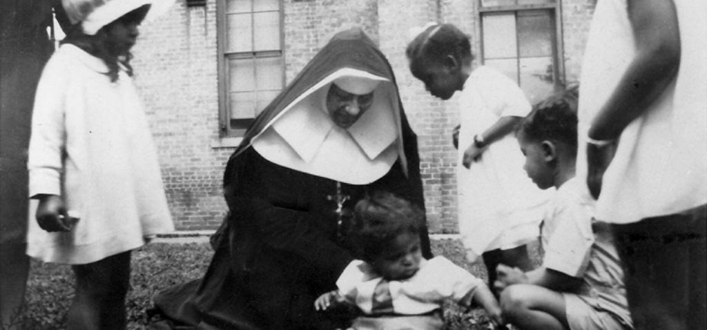 Saint Katharine Drexel catholic nun playing with children of color