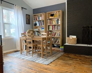 small table next to two bookshelves
