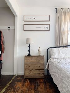 two wood signs above three drawer nightstand