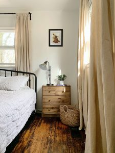 three drawer nightstand with lamp and picture above it