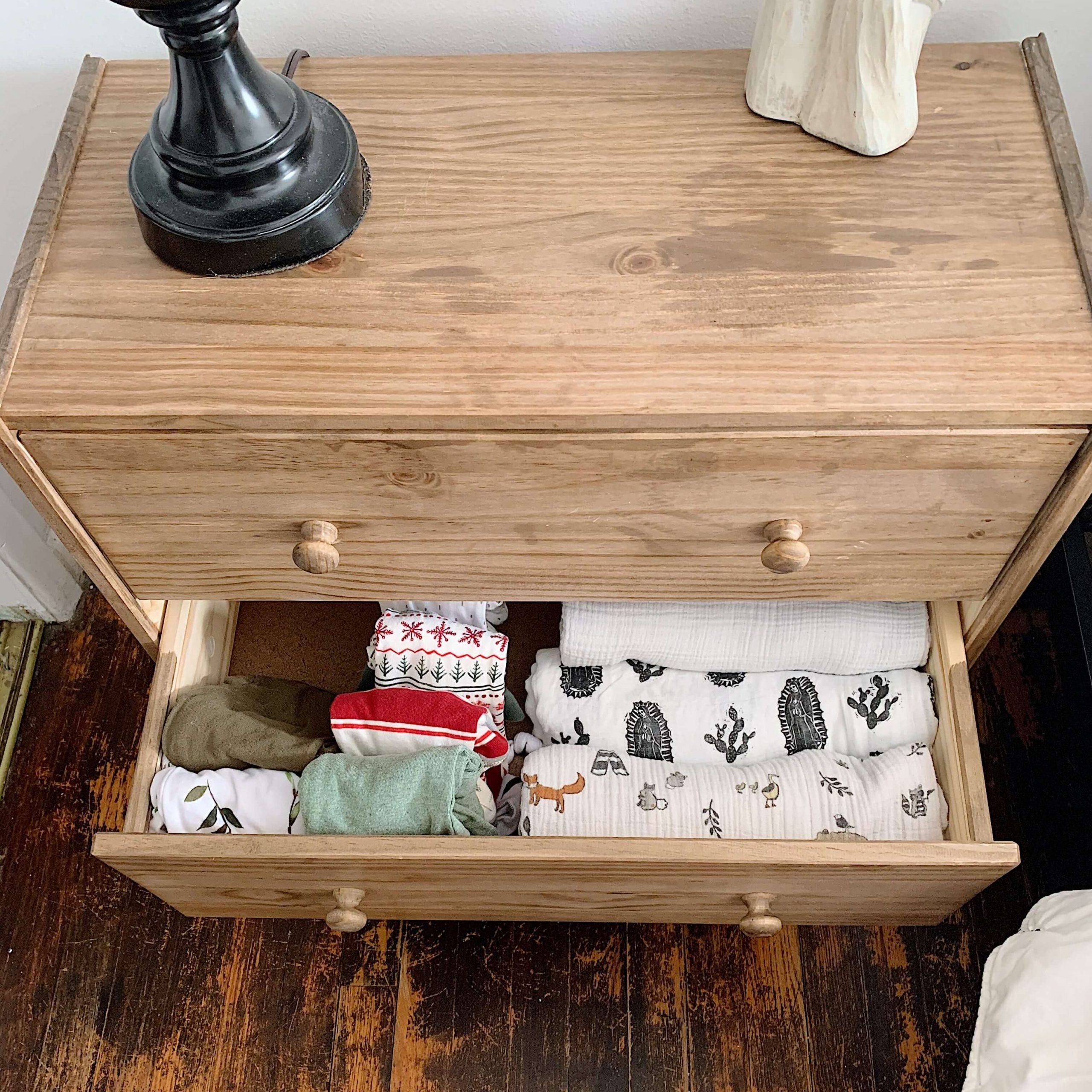 nightstand with baby clothes and blankets