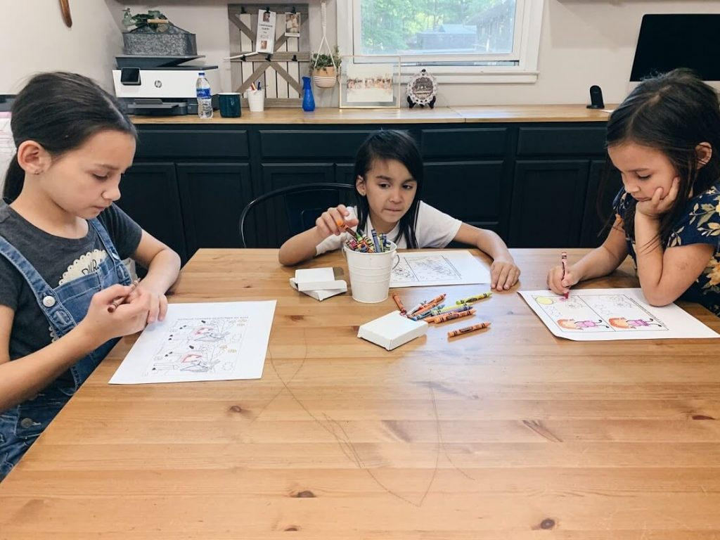 three young sisters coloring at a table